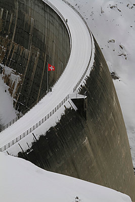 Swiss flag over snowy dam, Vals, Canton of Grisons, Switzerland - p301m2148996 by Gerhard Fitzthum