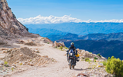 Man driving on touring motorbike on dirt road, Potosi, Bolivia - p429m1469420 by Henn Photography