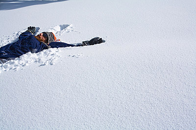 Snowboarder making a snow angel - p924m665204 by Mallon Industries