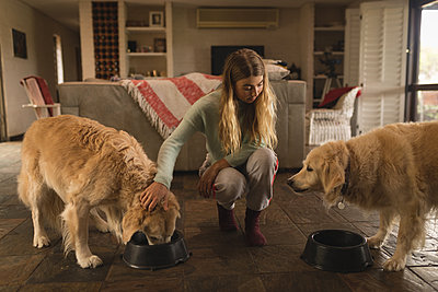 Teenage girl feeding her dogs at home - p1315m2003319 by Wavebreak