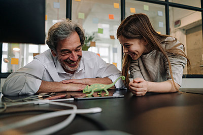 Happy senior buisinessman and girl playing with chameleon figurine in office - p300m2155276 by Gustafsson