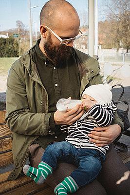 Father feeding baby - p312m2162274 by Amanda Falkman
