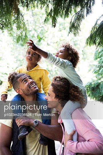 Happy parents carrying daughters on shoulders below trees in park - p1023m2238528 by Tom Merton