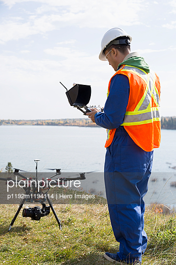 Surveyor with drone equipment at sunny lakeside - p1192m1194114 by Hero Images