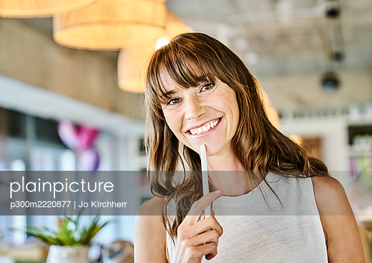 Smiling woman holding digitized pen while standing at home - p300m2220877 by Jo Kirchherr