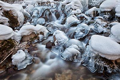 Fließendes Wasser eines Baches mit Schnee und Eis über den Steinen - p1383m1444551 von Wolfgang Steiner