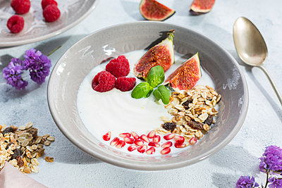 Bowl of natural yoghurt with fruit muesli, raspberries, figs and pomegranate seeds - p300m2060467 by JLPfeifer