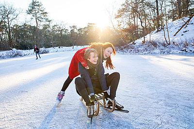 Cheerful couple enjoying sledding and ice-skating on frozen lake - p300m2287644 by Frank van Delft