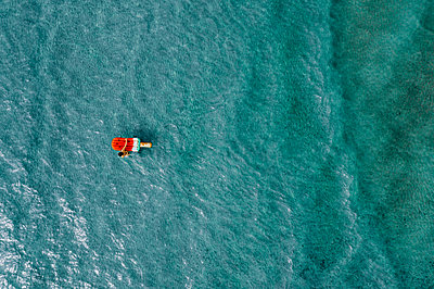 Woman on air mattress in the sea, drone photography - p713m2289237 by Florian Kresse