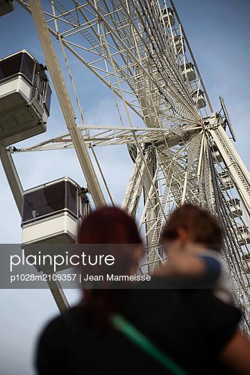Mother holding son at the funfair, Les Tuileries, Paris, France - p1028m2109357 by Jean Marmeisse