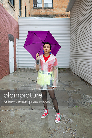Portrait confident young woman with purple umbrella wearing rain poncho in urban alley - p1192m2123442 by Hero Images