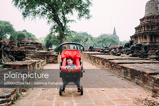 Thailand, Ayutthaya, Baby girl sleeping deeply on the stroller surrounded by ruins and buddha statues - p300m2004744 von Gemma Ferrando