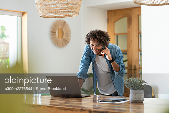 Male entrepreneur using laptop while talking on phone at home - p300m2276544 by Steve Brookland