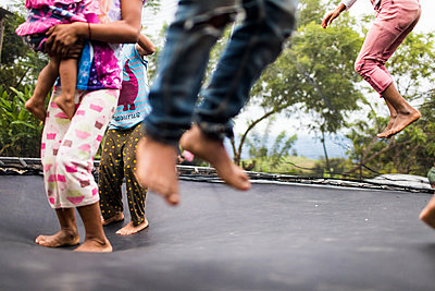 kids jumping on backyard trampoline. - p1166m2171564 by Cavan Images
