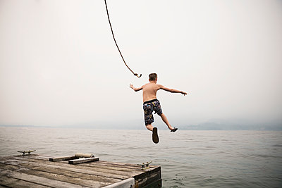 Boy jumping mid-air from dock into lake - p1192m1078339f by Hero Images
