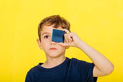 Close-up of cute boy holding blue acrylic glass against yellow background - p300m2199117 by Josep Rovirosa