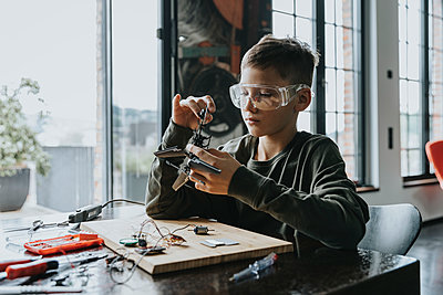 Boy assembling miniature helicopter at home - p300m2214201 by Mareen Fischinger