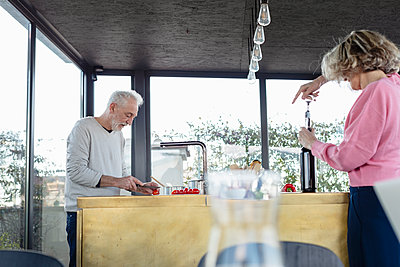 Senior couple working while standing in kitchen at home - p300m2265114 by Emma Innocenti