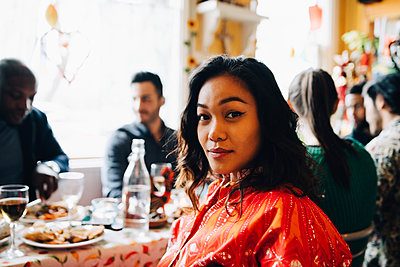 Portrait of confident young woman sitting at table against multi-ethnic friends enjoying brunch in restaurant - p426m2046338 by Maskot