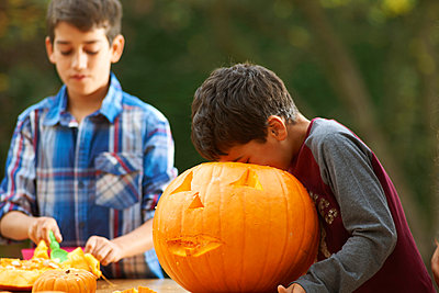 Siblings hollowing out pumpkin - p429m1006373f by Peter Muller