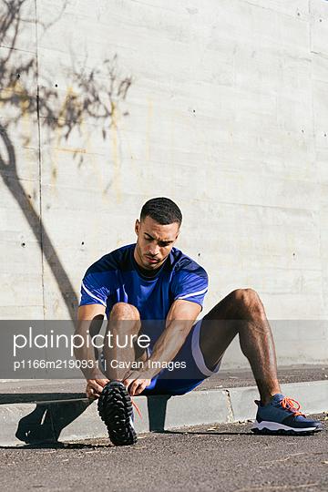 Full length of African American athlete tying shoelaces - p1166m2190931 by Cavan Images