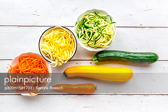 Zoodles, green and yellow zucchini, carrot on white wood - p300m1581733 von Sandra Roesch