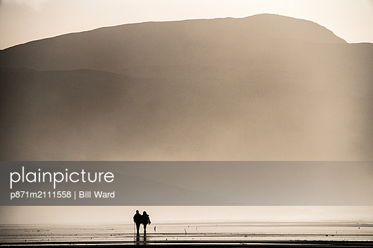 Couple taking a Sunday afternoon walk on Traigh Eais, Barra, Outer Hebrides, Scotland, United Kingdom - p871m2111558 by Bill Ward