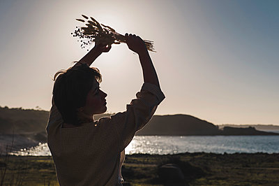 France, Brittany, Sunset, Young woman with bouquet of flowers on the seashore, portrait - p1150m2264250 by Elise Ortiou Campion