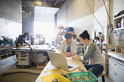 Female design professional engineers brainstorming at workbench in workshop - p1192m1202055 by Hero Images