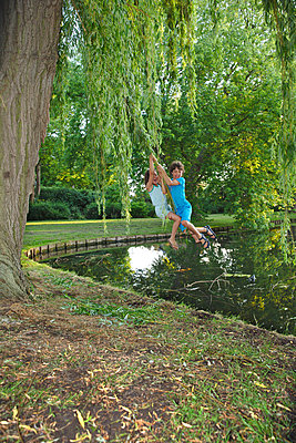 Children swinging on a branch of a weeping-willow above a pond - p1231m2191454 by Iris Loonen