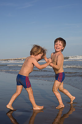 Kids playing at the beach - p1308m2126690 by felice douglas