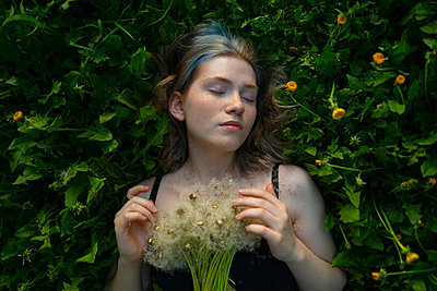 Young woman with closed eyes lying in the meadow - p1646m2264260 by Slava Chistyakov