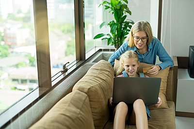 Mother and daughter in modern living room on a couch with laptop and credit card - p300m1586954 by Steve Brookland