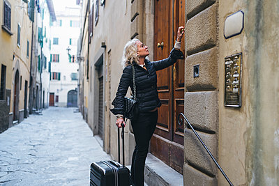 Italy, Florence, mature woman dressed in black  standing in front of entrance door with rolling suitcase - p300m2102887 by Francesco Buttitta