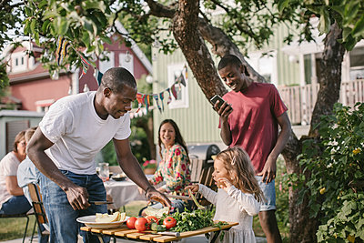 Boy photographing sister and father preparing food at table in backyard during garden party - p426m2036541 by Maskot