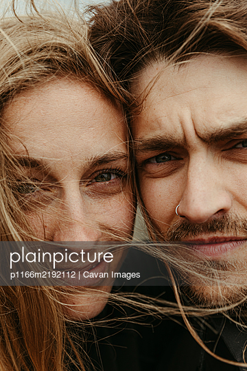 up close of man and woman with eyes next to each other and windy hair - p1166m2192112 by Cavan Images