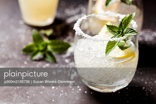 Margarita cocktails with lemon and mint leaves - p300m2155736 by Susan Brooks-Dammann