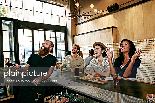 Smiling bartender and customers watching television in bar - p555m1305266 by Peathegee Inc