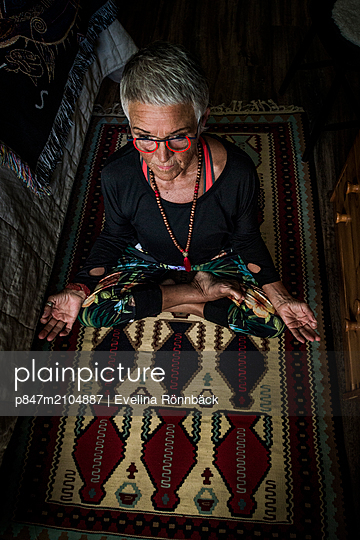 Relaxed Old Woman Practising Yoga At Home   - p847m2104887 by Evelina Rönnbäck