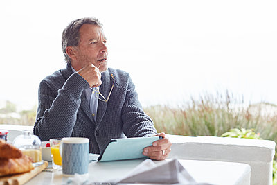 Pensive senior man using digital tablet at breakfast on patio - p1023m1217911 by Ryan Lees