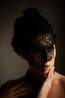 Portrait of woman wearing a black lace fascinator - p1047m1502848 by Sally Mundy