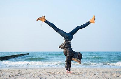 Frau macht Handstand am Strand - p427m902515 von Ralf Mohr