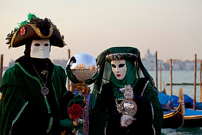 Venice, Veneto, Italy, A couple in costume during carnival at the bacino di San Marco with gondolas in the background. - p652m716790 by Ken Scicluna