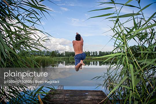 Young man jumping into lake, Brandenburg - p1093m2193609 by Sven Hagolani