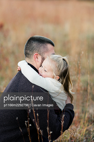 A father and his daughter hugging each other tightly - p1166m2292796 by Cavan Images