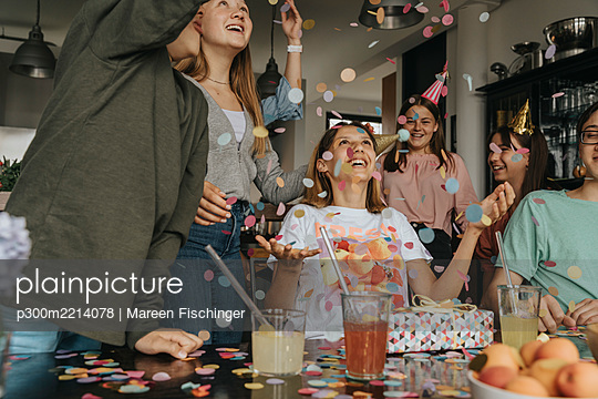 Friends throwing confetti on cheerful teenage girl in birthday party at home - p300m2214078 by Mareen Fischinger