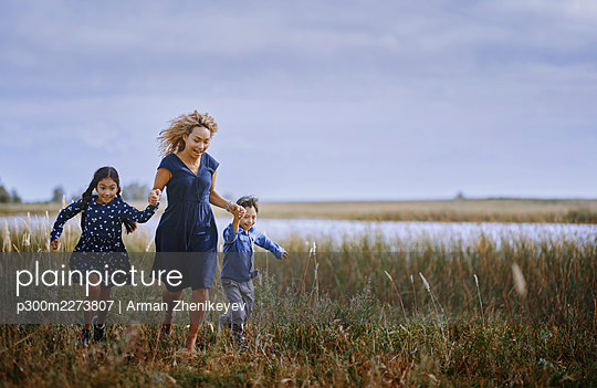 Mother holding hands while running with daughter and son on grass - p300m2273807 by Arman Zhenikeyev