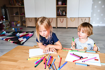 Little boy with sister drawing with felt-tip pens - p1166m2159624 by Cavan Images