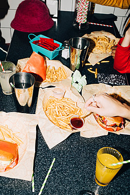 High angle view of friends eating french fries at table in cafe - p426m2194818 by Maskot
