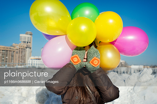 Woman with colorful balloons covering face with hands in park - p1166m968668f by Cavan Images
